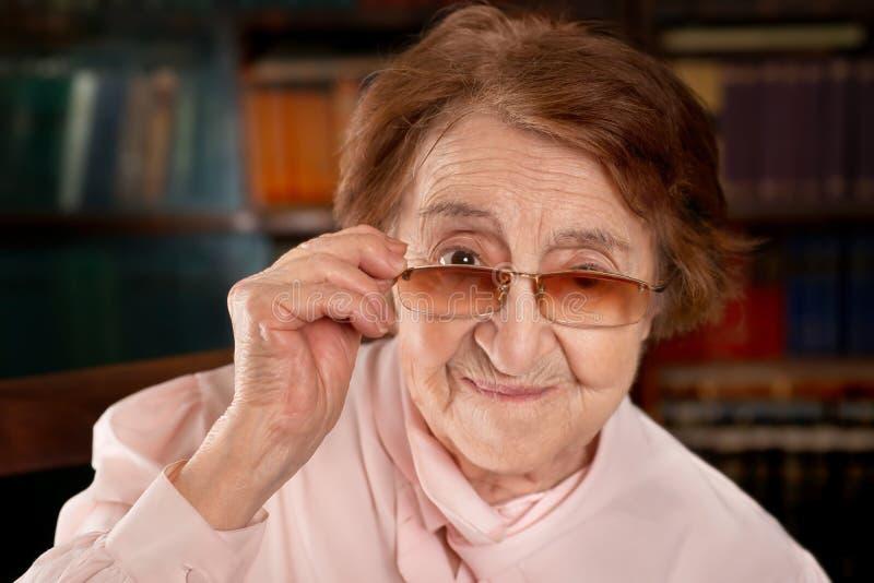 Старшая усмехаясь женщина рассматривая стекла стоковая фотография rf