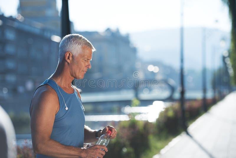 Старшая jogging свежая вода человека выпивая от бутылки стоковые фотографии rf