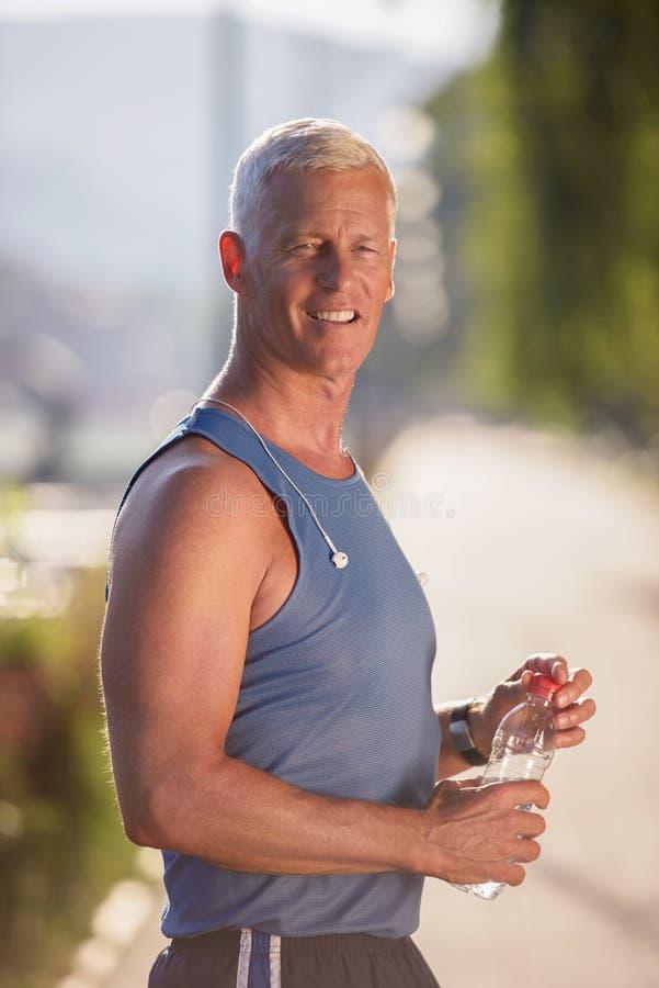 Старшая jogging свежая вода человека выпивая от бутылки стоковое фото rf
