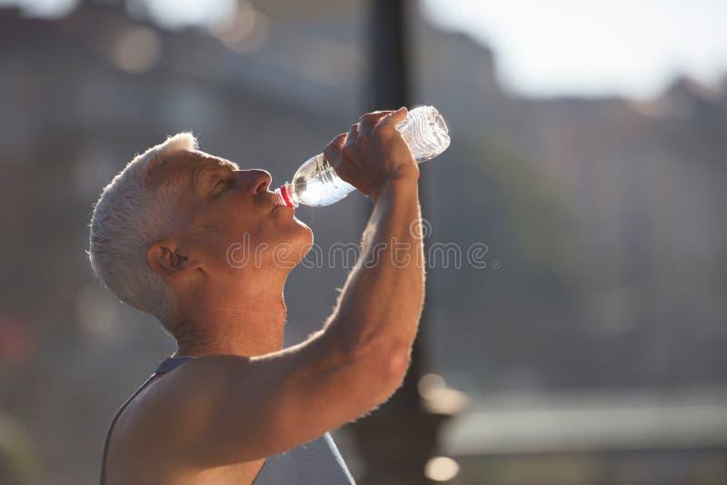 Старшая jogging свежая вода человека выпивая от бутылки стоковая фотография