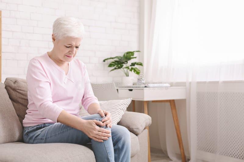 Старшее страдание женщины от боли в ноге, массажируя ее колено стоковые фото