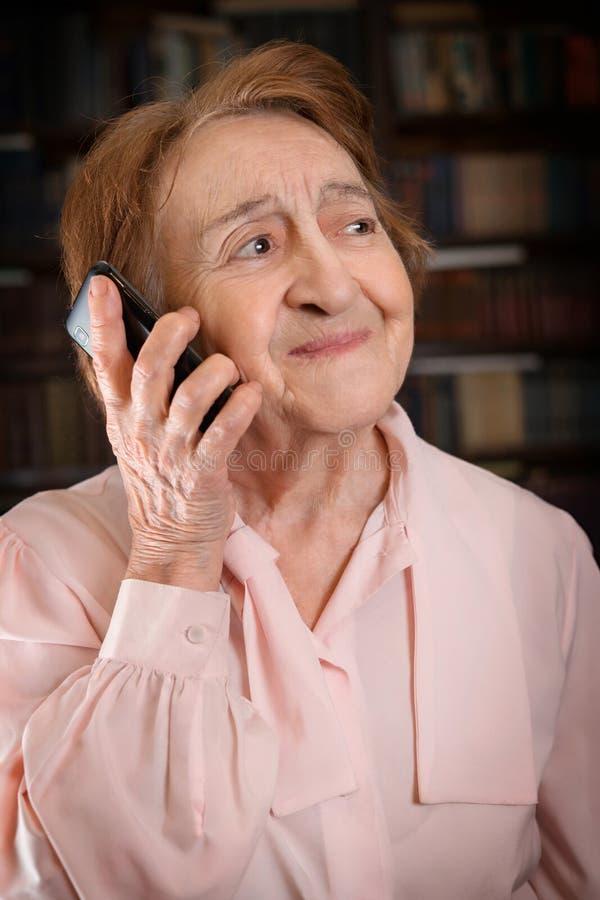 старшее smartphone используя женщину стоковые изображения