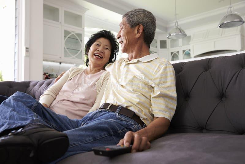 Старшие азиатские пары дома на софе смотря ТВ совместно стоковые фото