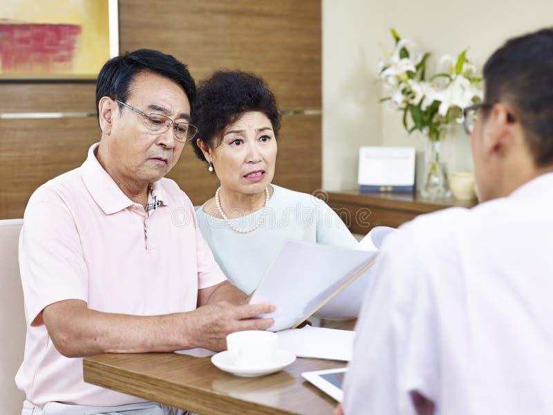 Старшие азиатские пары сотрясенные продавцом стоковое фото rf