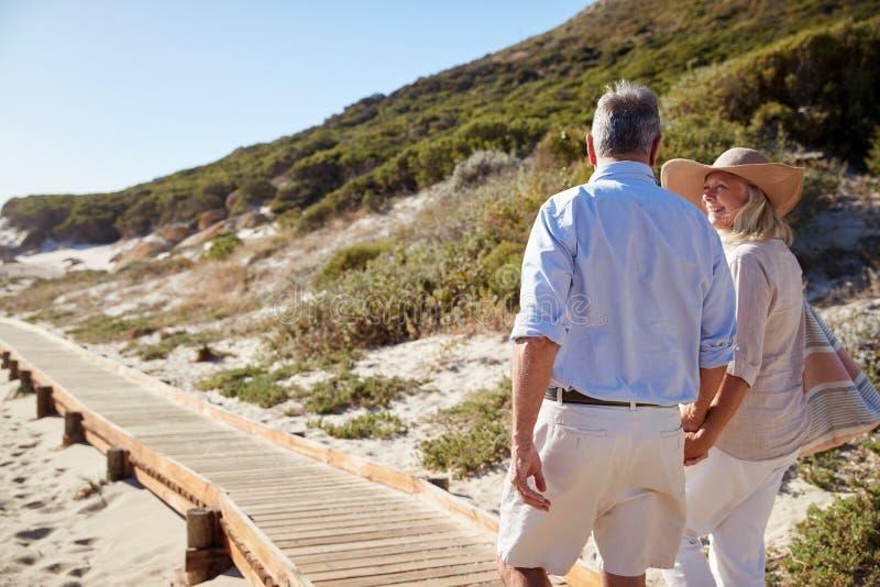 Старшие белые пары идя вдоль деревянной прогулки на пляже держа руки, конец вверх, взгляд задней части стоковые фотографии rf