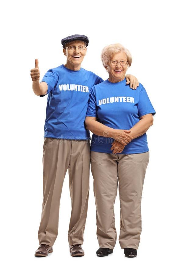 Старшие волонтеры усмехаясь на камере и давая большие пальцы руки вверх стоковое изображение rf