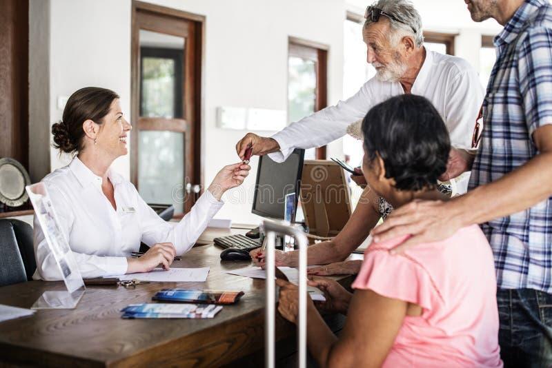 Старшие гости проверяя внутри на ем счетчик ресервирования стоковые изображения rf