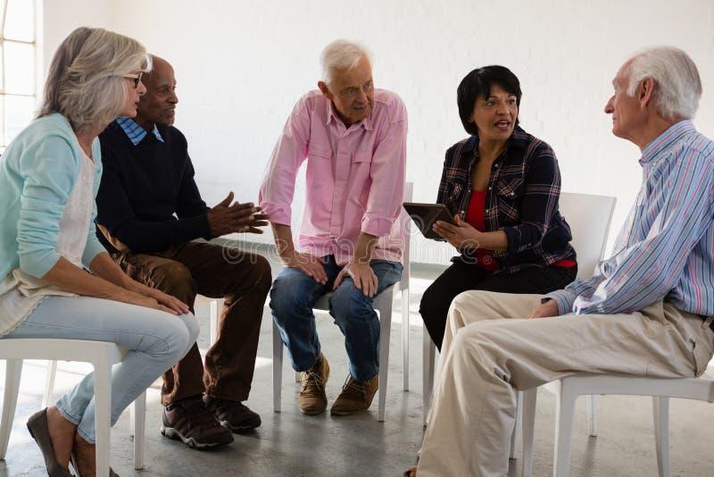 Старшие друзья обсуждая над планшетом пока сидящ на стуле стоковое фото