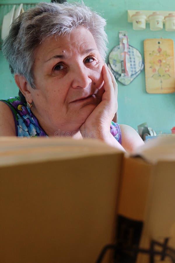 Старшие женщины при книга смотря камеру стоковая фотография