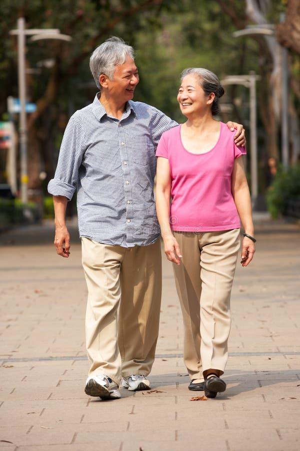 Старшие китайские пары гуляя в парк стоковая фотография