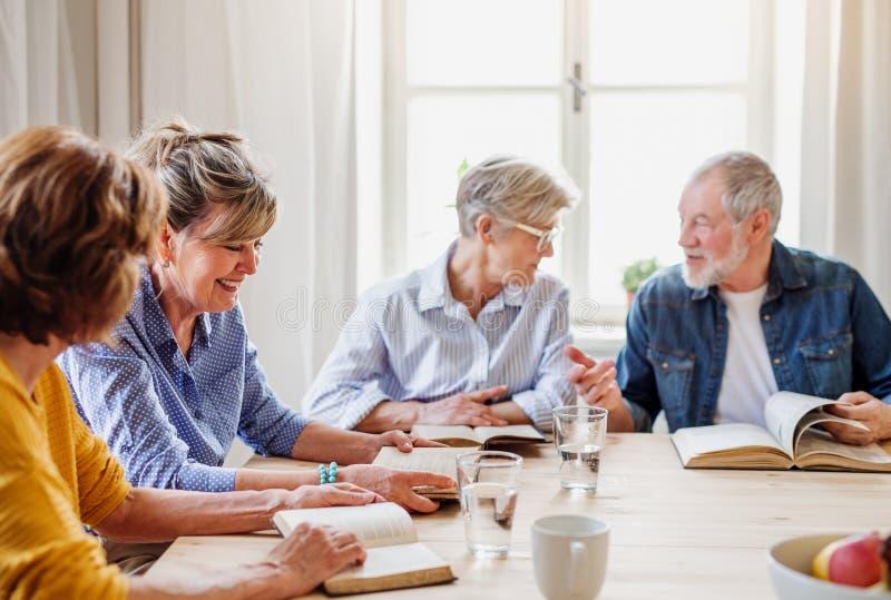 Старшие люди в группе чтения библии в клубе общественного центра стоковые изображения