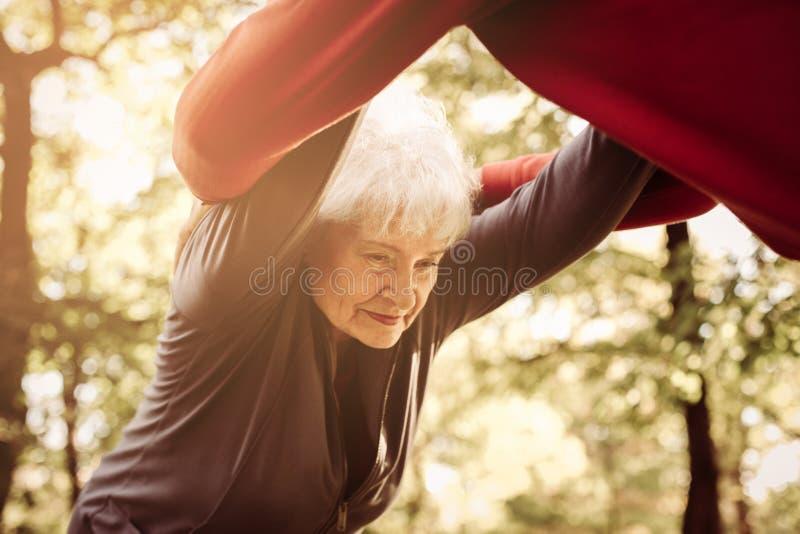 Старшие люди работая совместно в луге держа руки стоковое изображение