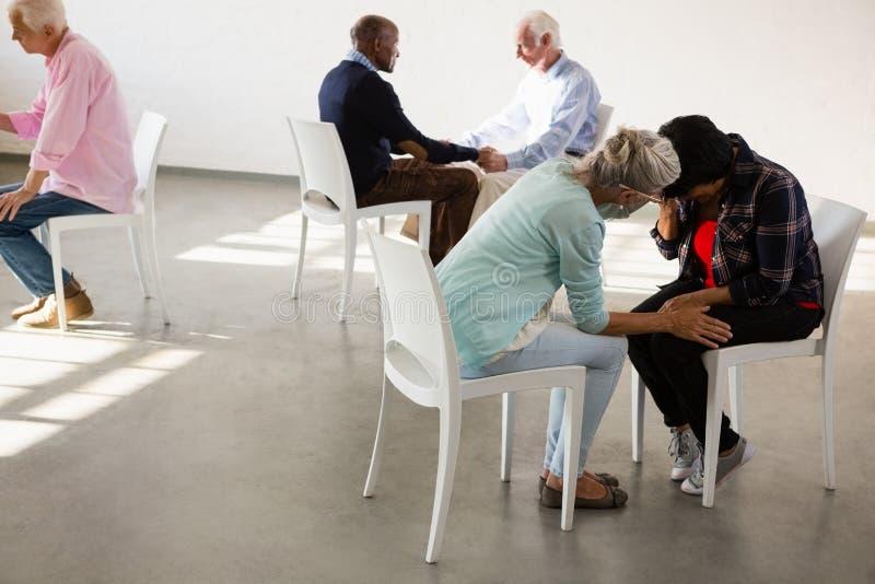 Старшие люди сидя лицом к лицу стоковые изображения