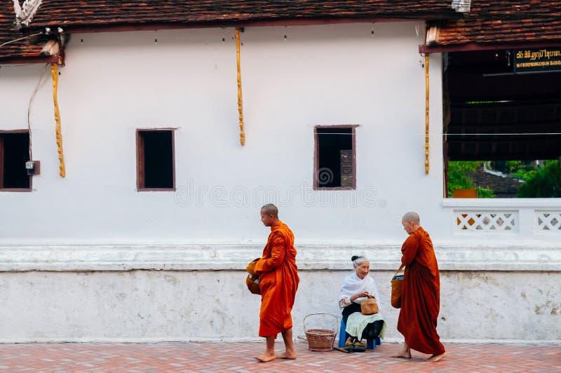 Старшие местные люди в традиции милостынь утра давая еду монахам стоковое изображение