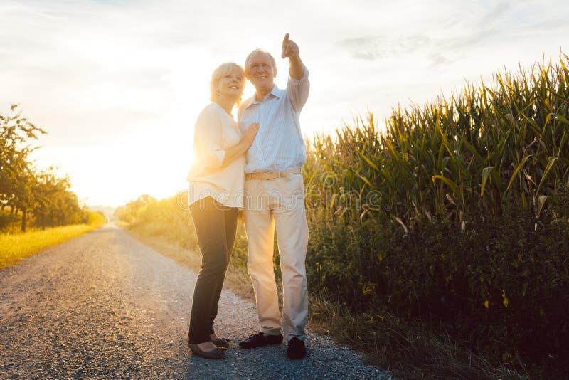 Старшие пара наслаждаются вечерней прогулкой по сельской местности стоковое фото rf