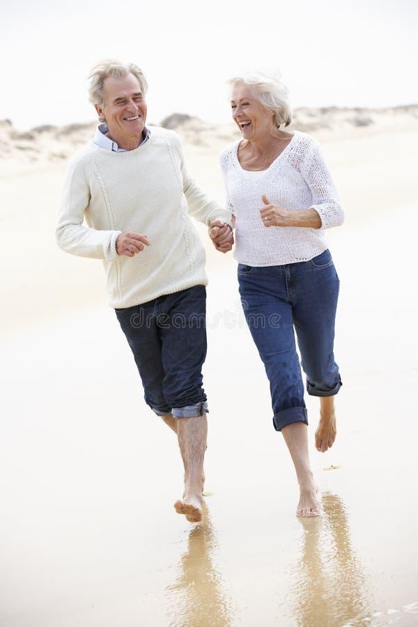 Старшие пары бежать вдоль пляжа совместно стоковая фотография