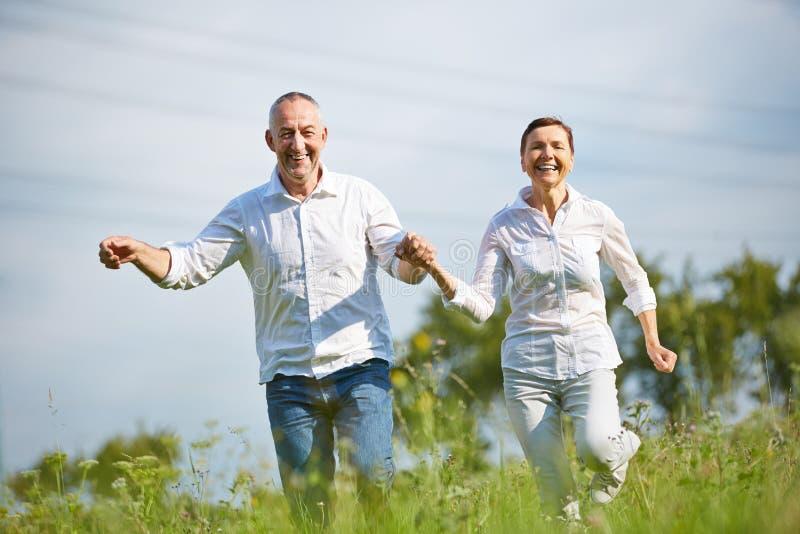 Старшие пары бежать над лугом стоковое фото