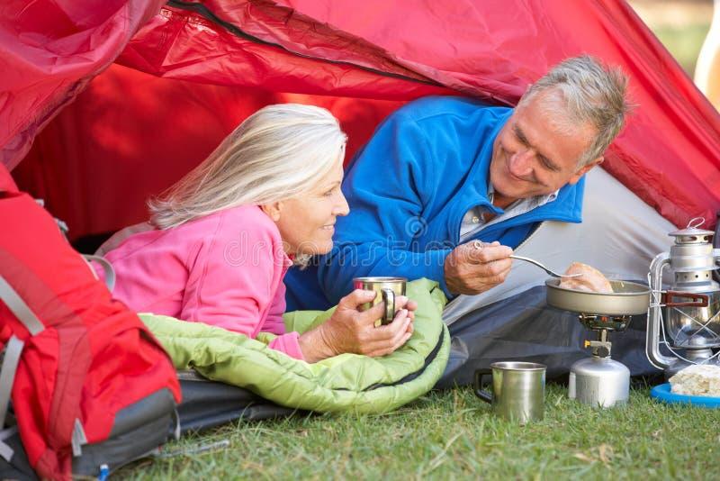 Старшие пары варя завтрак на располагаясь лагерем празднике стоковое изображение