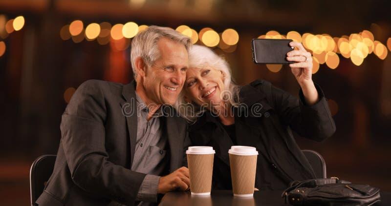Старшие пары вне на дате вечера принимая selfies с smartphone стоковые фото