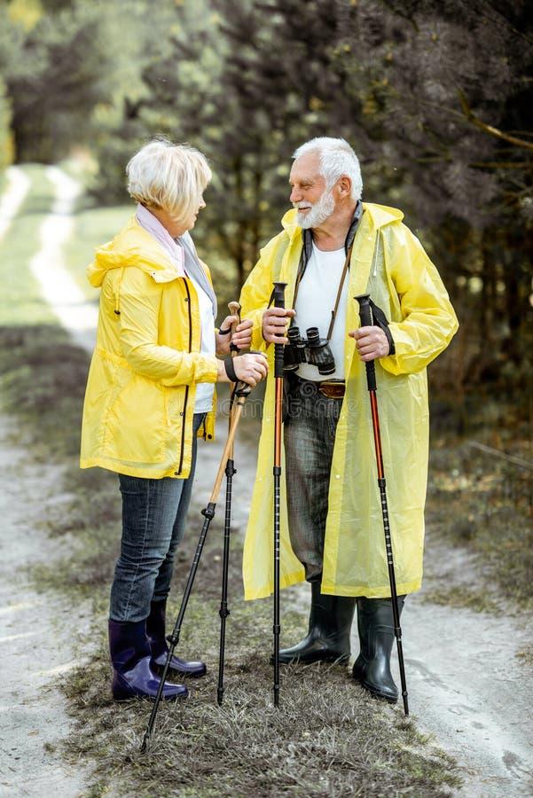 Старшие пары в плащах в лесе стоковое изображение
