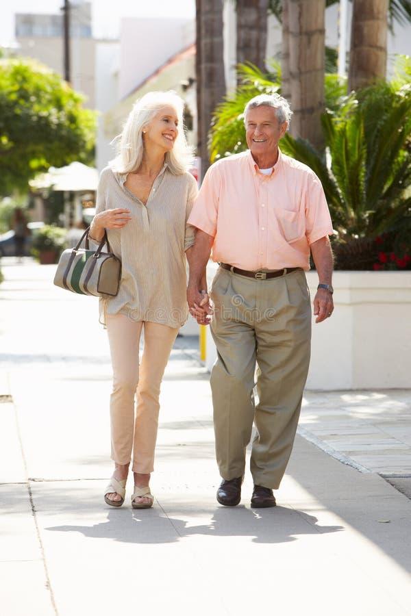 Старшие пары гуляя вдоль улицы совместно стоковое фото rf