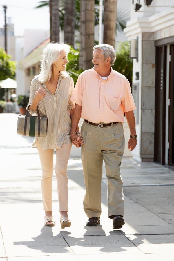 Старшие пары гуляя вдоль улицы совместно стоковые фотографии rf