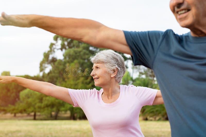 Старшие пары делая протягивающ тренировку стоковое изображение