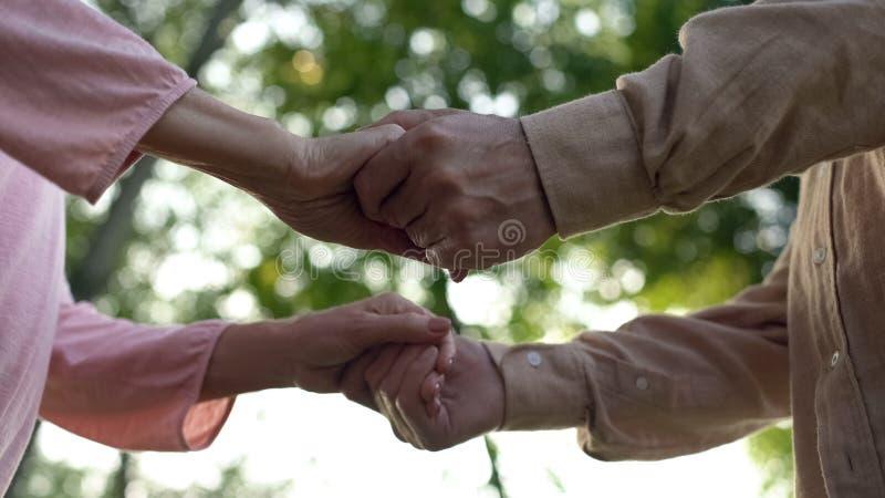 Старшие пары держа руки, встречая старость совместно, близкие отношения, забота стоковое фото