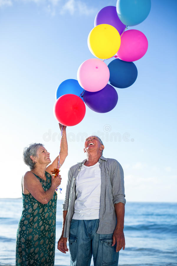 Старшие пары держа воздушные шары стоковые изображения