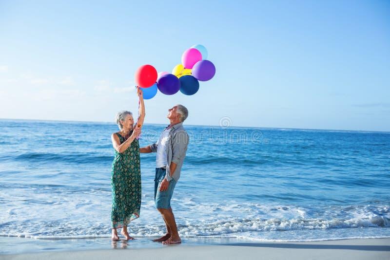 Старшие пары держа воздушные шары стоковая фотография