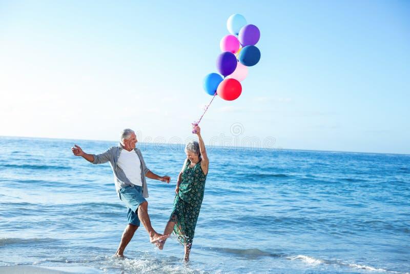 Старшие пары держа воздушные шары стоковое фото