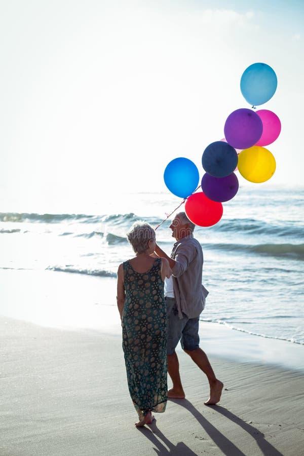 Старшие пары держа воздушные шары стоковые фото