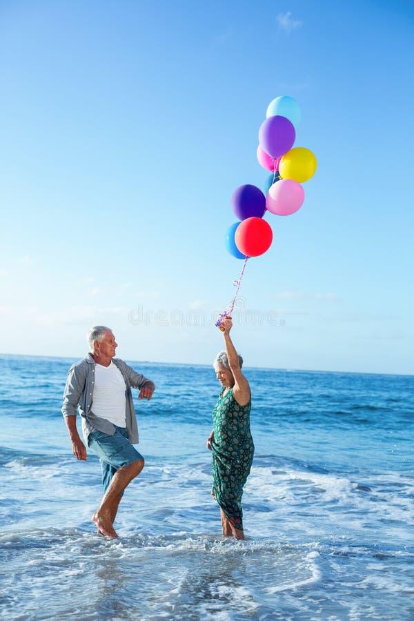 Старшие пары держа воздушные шары стоковое изображение