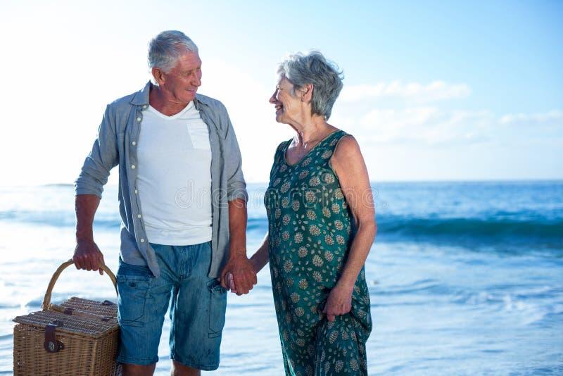Старшие пары держа корзину пикника стоковое фото rf