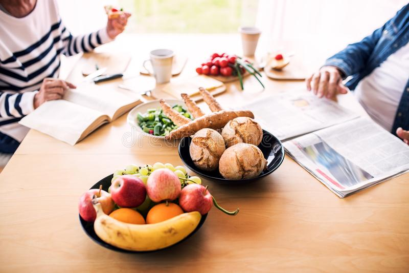 Старшие пары есть завтрак дома стоковое изображение rf