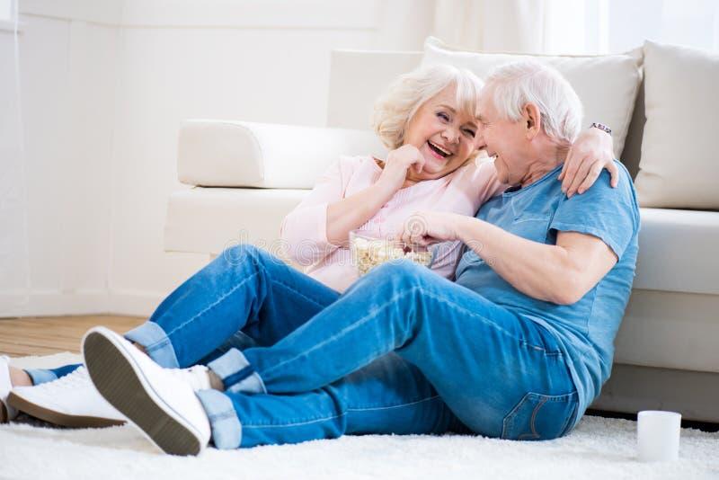 Старшие пары есть попкорн и сидя на поле стоковое изображение