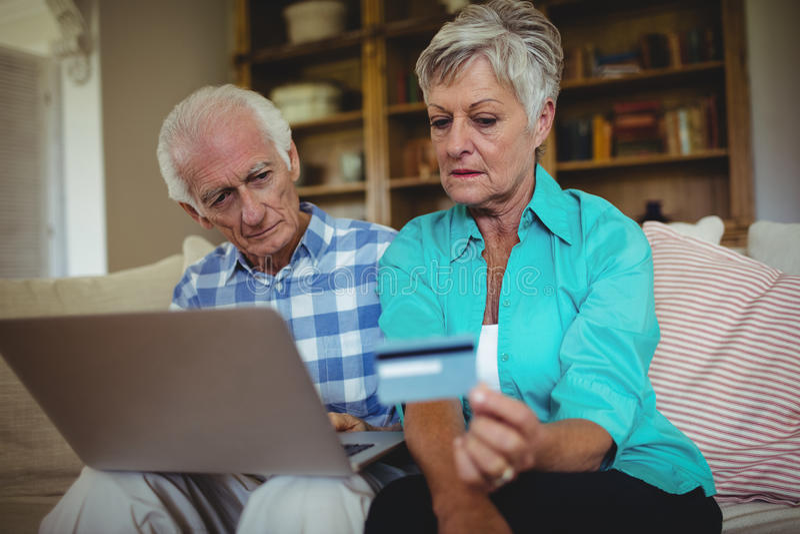 Старшие пары делая онлайн покупки на компьтер-книжке стоковое фото