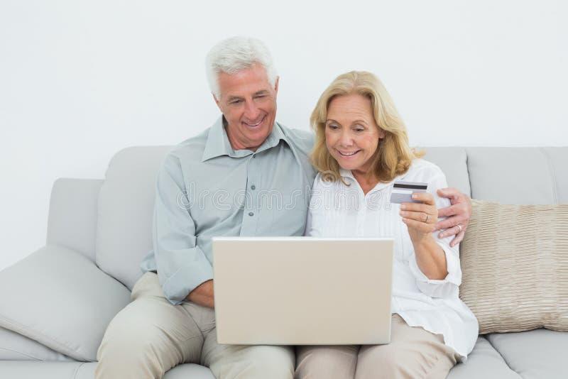 Старшие пары делая онлайн покупки на софе стоковые фотографии rf