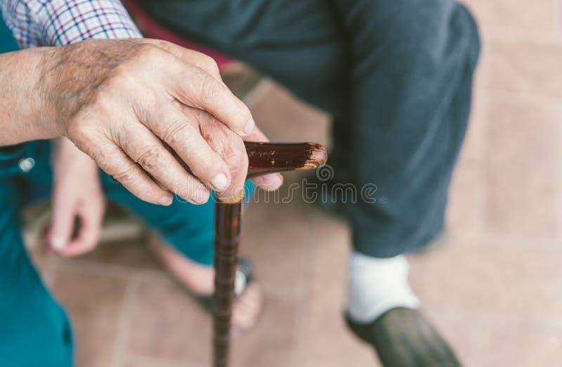 Старшие пары закрывают вверх держащ каждые другие руки на тросточке стоковые фото