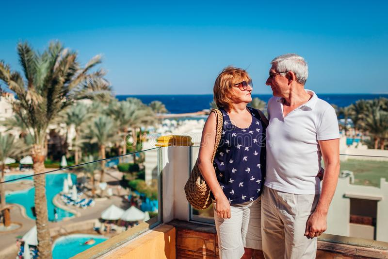 Старшие пары идя на территорию гостиницы восхищая вид на море Люди наслаждаясь каникулами перемещать стоковое изображение rf