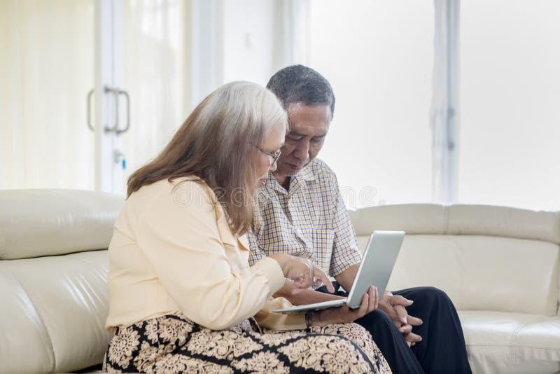 Старшие пары используя ноутбук на софе стоковое изображение