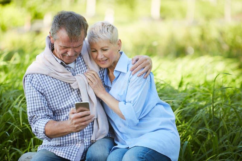 Старшие пары используя Outdoors смартфона стоковое фото