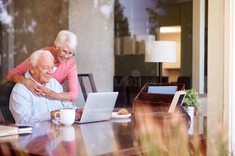 Старшие пары используя компьтер-книжку на столе дома стоковое фото