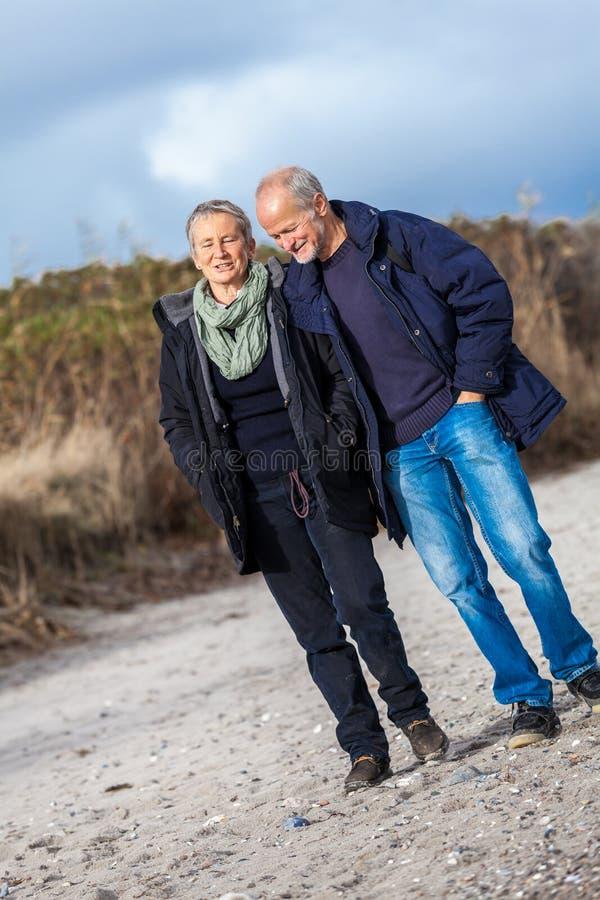 Download Старшие пары идя на осень пляжа Стоковое Фото - изображение насчитывающей семья, жизнерадостно: 37929468
