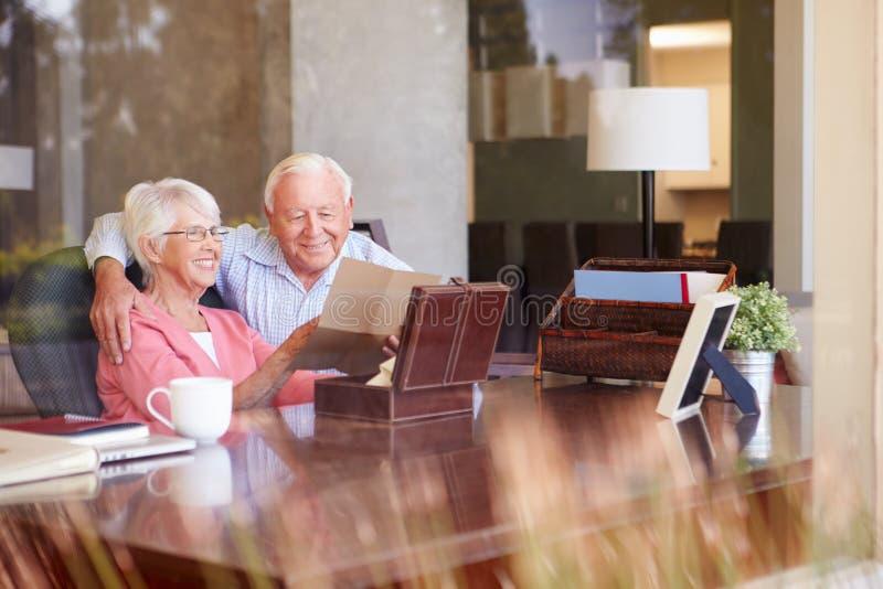 Старшие пары кладя письмо в коробку Keepsake стоковые фотографии rf