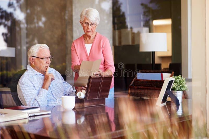 Старшие пары кладя письмо в коробку Keepsake стоковое фото