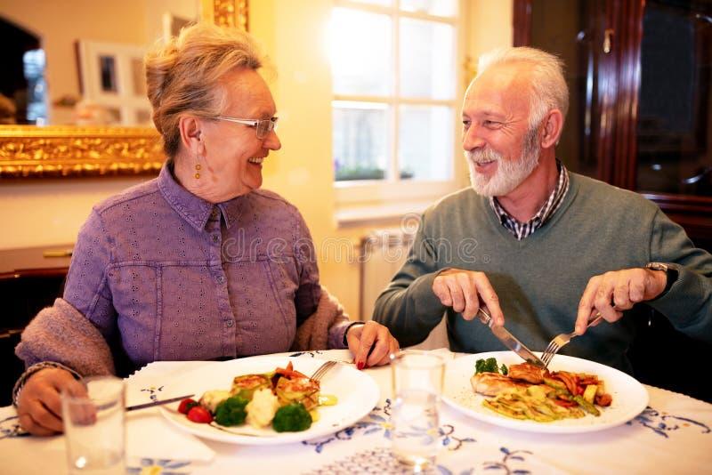 Старшие пары наслаждаясь вкусной едой каждым стоковые фотографии rf