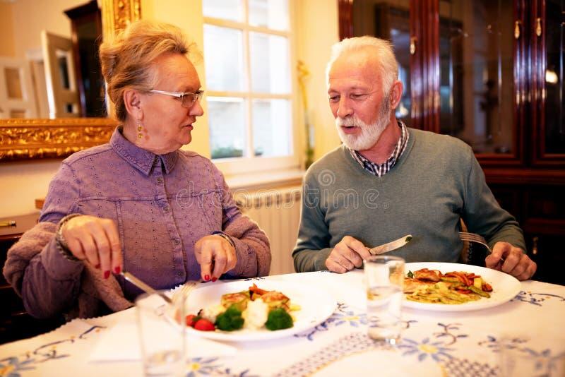 Старшие пары наслаждаясь вкусной едой каждым стоковые фото