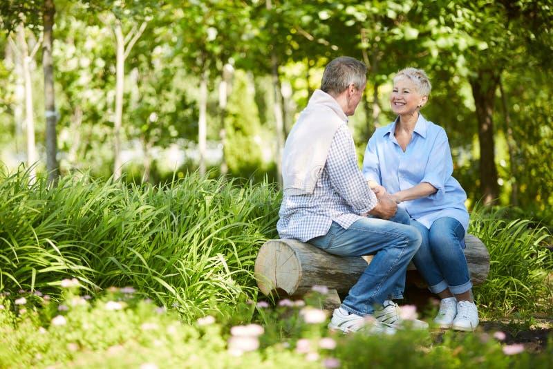 Старшие пары наслаждаясь датой в парке стоковые изображения