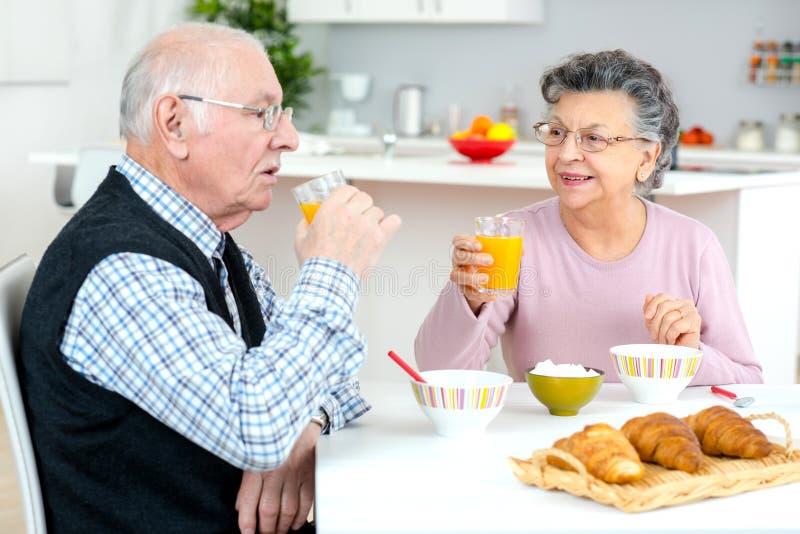 Старшие пары наслаждаясь завтраком дома стоковое фото rf